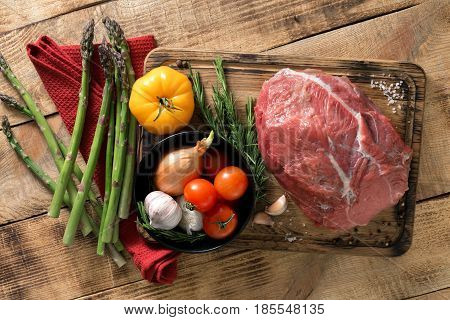 Fresh raw beef tenderloin with different vegetables on wooden table top view. Ingredients for cooking healthy food