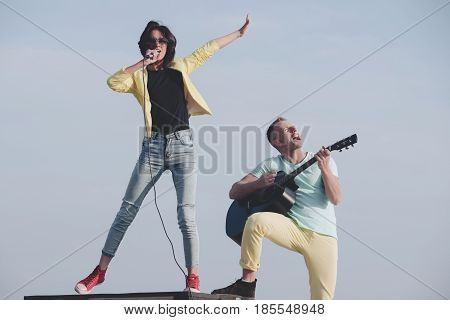 Young Couple Of Musicians Performing On Idyllic Blue Sky