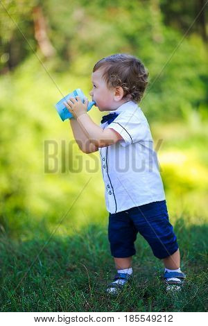 Little boy drinking water from blue blue no-spill cup. Toddler make first steps. Curly boy on a background of green bushes. One year old kid holding the baby cup. Adorable curly hair boy being thirsty.