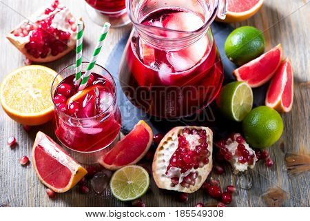 Sangria or lemonade in pitcher with ice and citrus fruits homemade refreshing lemonade drink with pomegranate juice