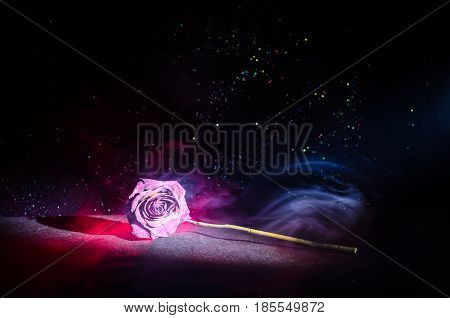 A wilting rose signifies lost love divorce or a bad relationship dead rose on dark background with smoke poster