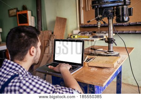Photo of a carpenter using laptop at his workshop.