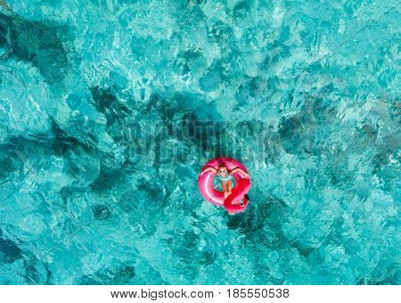 Top view of adorable little girl swimming in tropical ocean in Maldives