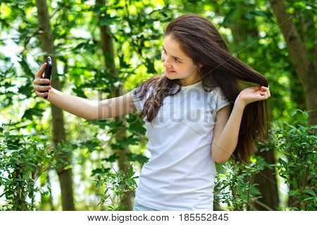 Girl walks in the park and makes selfie happy.
