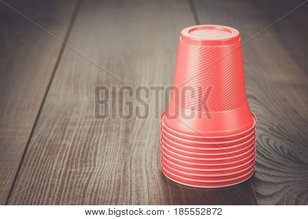 disposable plastic cups. red plastic cups on the wooden table. party plastic cups. stack of plastic cups