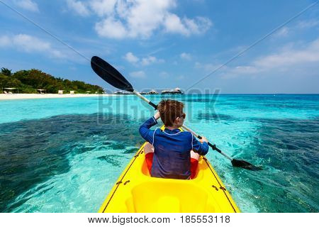 Back view of happy teenage boy on a kayak at tropical lagoon