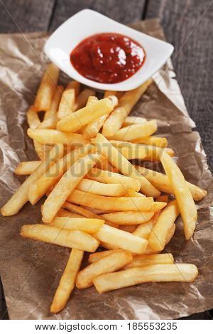 French fries, fried potato sticks served on parchment paper with bowl of ketchup
