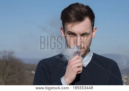 man vaping smoking electronic cigarette with vapor cloud and squinting eyes on sunny summer day outdoors on blue sky background. Health safety and addiction