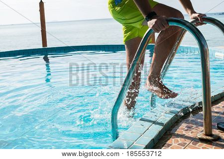 Photo of guy in swimming shorts at outdoor pool