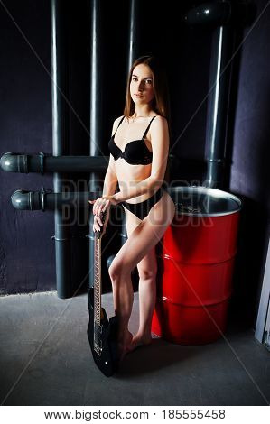 Portrait Of Sexy Brunette Girl At Black Underwear With Guitar Near Red Stell Barrel. Fashion Model S