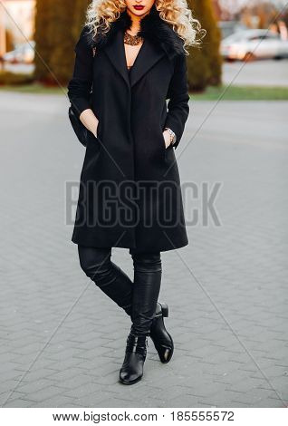 Portrait of a fashionable woman posing outdoors in a black autumn coat trend, leggings, fall boots, a necklace. Photography for catalog, advertising
