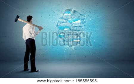 Business man hitting grungy brick wall with huge hammer