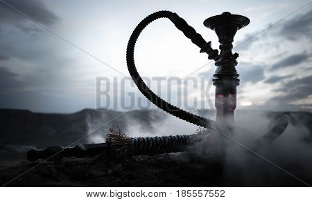 Hookah traditional arabic waterpipe direct sunset light outdoor photo. Mountain background