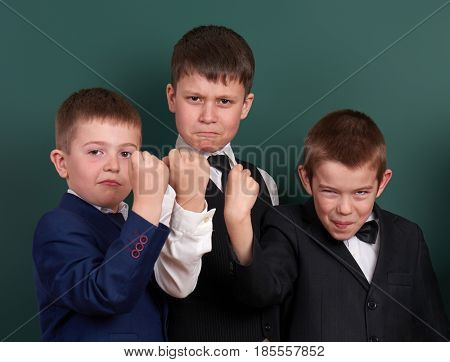 group pupil as a gang, show knuckle, posing near blank chalkboard background, grimacing and emotions, dressed in classic black suit
