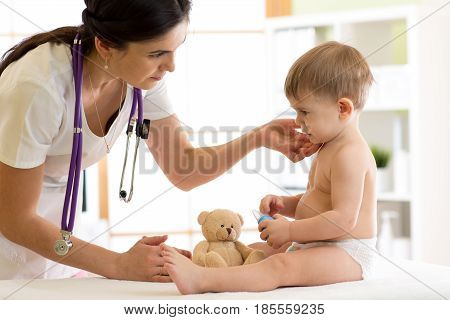 Doctor paediatrician checking boy's neck in hospital clinic