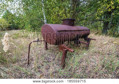 Old tank in collective farm near Zymovyshche ghost village in Chernobyl Exclusion Zone Ukraine