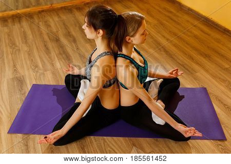 Young women in lotus pose on purple rug