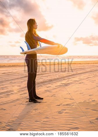 Beautiful young woman surfer girl in wetsuit with surfboard on a beach at sunset or sunrise. Lifestyle photo