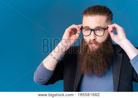 Taking life seriously. Portrait of handsome young man in formalwear adjusting his glasses while standing against blue background