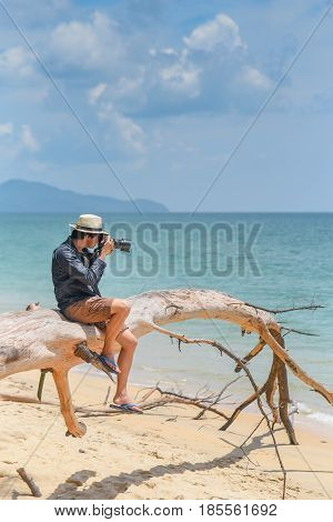 young man photographer with jean shirt and hat sitting on white dead tree near sandy beach of tropical island and take photos of turquoise sea summer holiday and vacation travel concepts