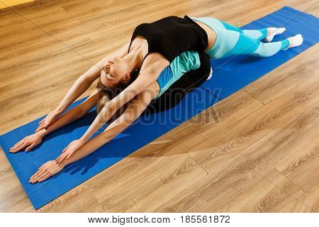 Two sportswomen practicing in yoga at gym