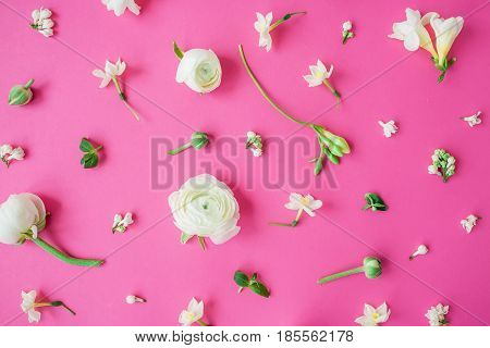 Floral pattern of white ranunculus, snapdragon, freesia and buds on pink background. Flat lay, top view. Summer background.