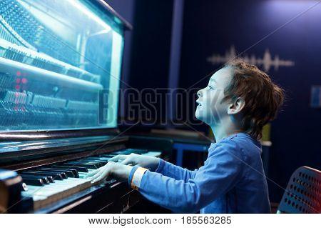 Boy playing on light music piano at playground