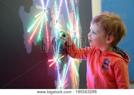 Boy Touching Glowing Map