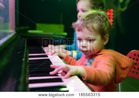 Brothers playing on light music piano at playground