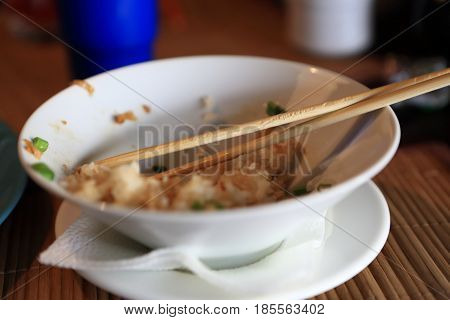 Leftovers of rice and chopsticks in the plate