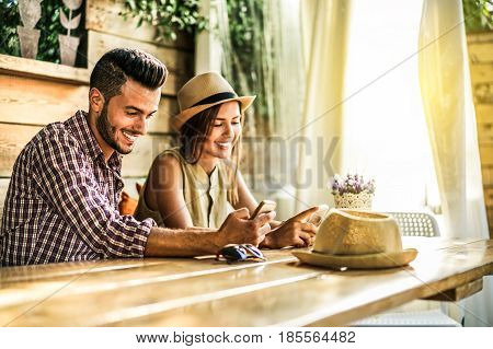 Young couple using mobile smartphones in bar cafe restaurant - Travel people sharing media in social networks with cell phones - Technology addiction concept - Focus on man face - Vintage filter