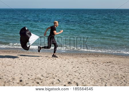 Side view of a person running on the seaside with speed training resistance parachute.