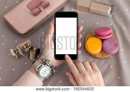 female hand with jewelry holding the phone with isolated screen