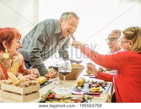 Happy senior friends having barbecue lunch at home - Old people having fun eating tasty meat skewers at bbq meal - Joyful elderly active lifestyle concept - Focus on man face - Warm contrast filter