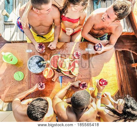 Happy friends toasting sangria wine and eating fresh watermelon fruit - Rich young people having fun in summer party day - Exclusive vacation concept - Warm filter with focus on glasses hands