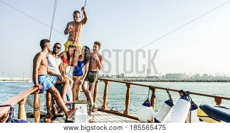 Happy friends drinking and having fun in boat party outdoor - Young rich people enjoying summer vacations toasting sangria red wine - Youngholidays and fest concept - Warm contrast filter