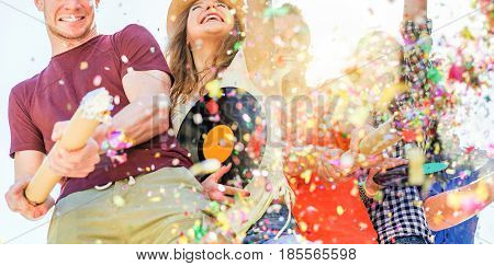 Group of happy friends enjoying party and throwing confetti - Young people having fun outdoor dancing and listening music at sunset - Friendship and youth concept - Main focus on two right guys faces