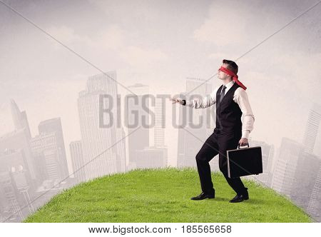 Young blindfolded businessman steps on a a patch of grass with a cloudy city in the background