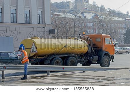 Nizhny Novgorod, Russia April 11, 2017: Work in the orange vest against the background of special equipment for cleaning water jet washing, a border of the aluminum at the edge of the highway. Russia