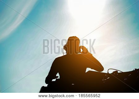 Silhouette of dj mixing outdoor with back sun light - Portrait of disc jockey playing old style vinyl music music for people on beach party at sunset - Fun and summerentertainment and fest concept
