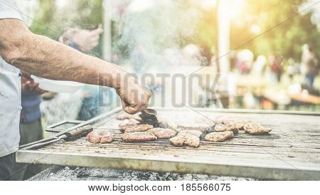 Man cooking meat at dinner barbecue - Chef grilling meat in park outdoor - Concept of eating bbq outdoor during summer time - Warm filter with back sun light - Focus on hand - Vintage filter