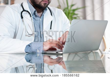 Doctor working on desk with laptop computer in doctors office. Medical doctor concept