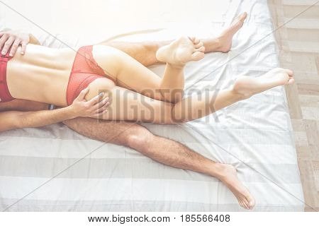Legs view of two lovers before sex - Passionate couple having sexual moments inside bedroom - Love and sexualitysentimental concept - Focus on man right hand - Warm cinematic vintage filter