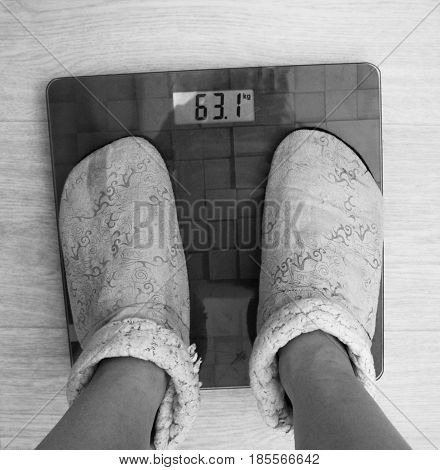 a person stands on the scale, weight 63 kg