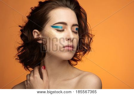 Young female model with hydrogel eye patches and eye makeup posing sensually on plain background.