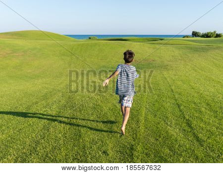 Child running on the grass field
