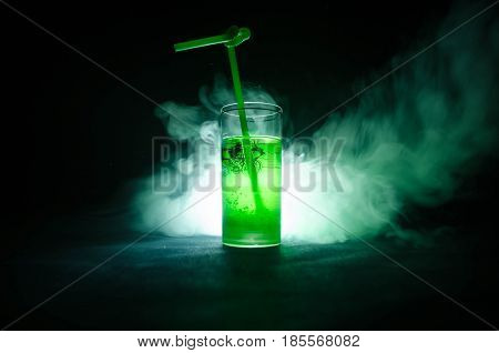 Glass Of Green Cocktail With Straw On Dark Background With Smoke And Backlights.