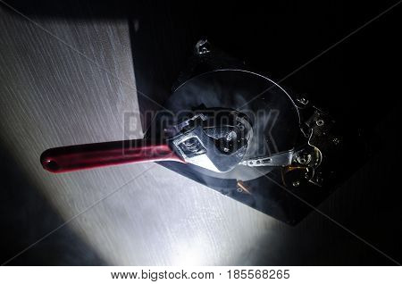 Adjustable Wrench Turn Off A Hard Disk. On A Dark Background. Computer Repair Concept