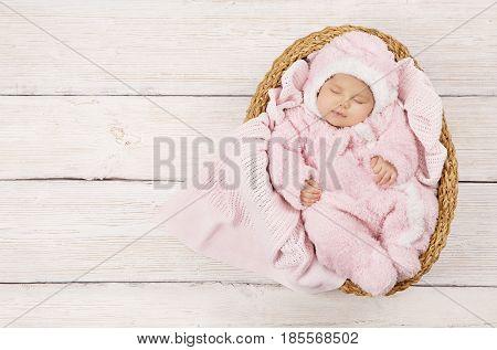 Baby Sleeping Newborn Kid Sleep in Pink Clothing New Born Child Asleep in Basket over Wood Background