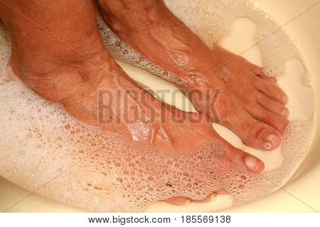 Therapeutic foot bath. Pedicure. Medical hygienic procedure. Washing feet. Patients with old feet with calluses.